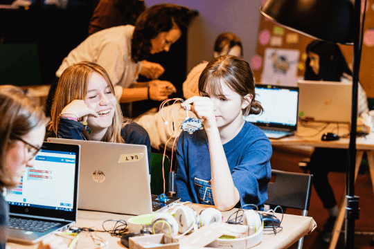 Zwei tüftelnde Mädchen sitzen lachend fasziniert vor einem Laptop und versuchen sich am Programmieren eines calliope mini Controllers.