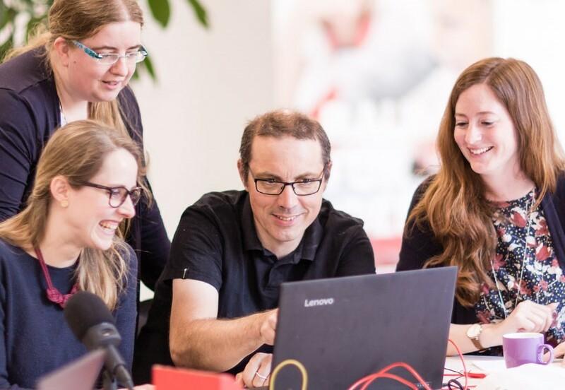 Ein Mentor schaut mit Fortbildungsteilnehmer*innen auf einen gemeinsam genutzten Latptop.