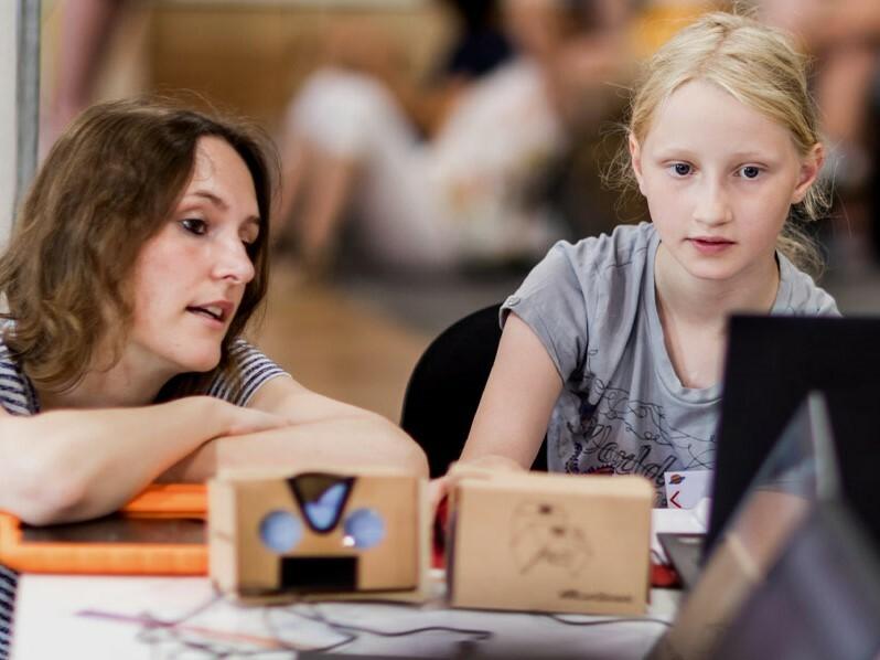 Eine Lehrerin und eine Schülerin arbeiten gemeinsam an einem Projekt am Computer.